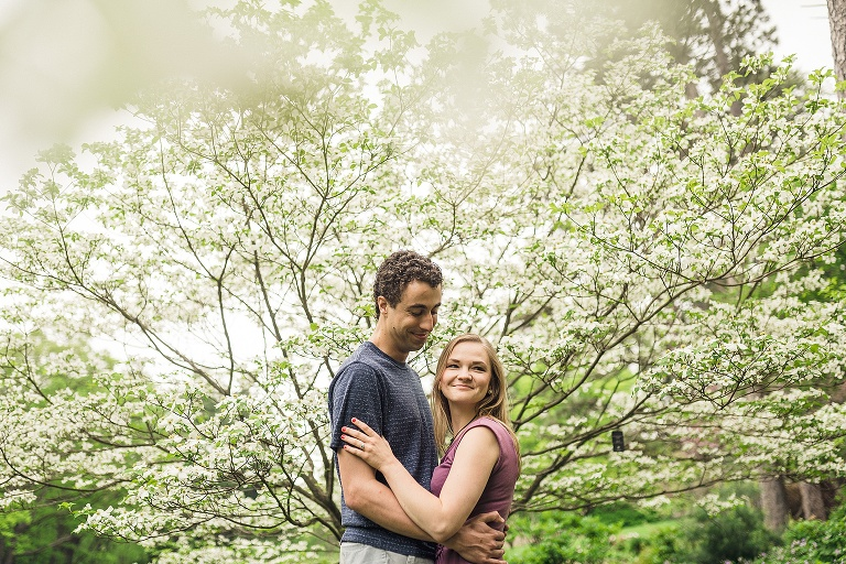 couple smiling in front of flowering tree at the Nichols arboretum